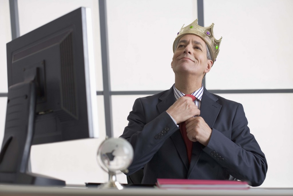Businessman with crown sitting at desk